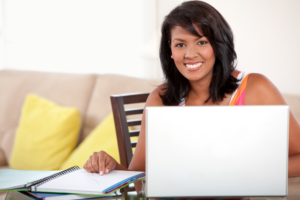 Beautiful smiley woman studying at home with a laptop