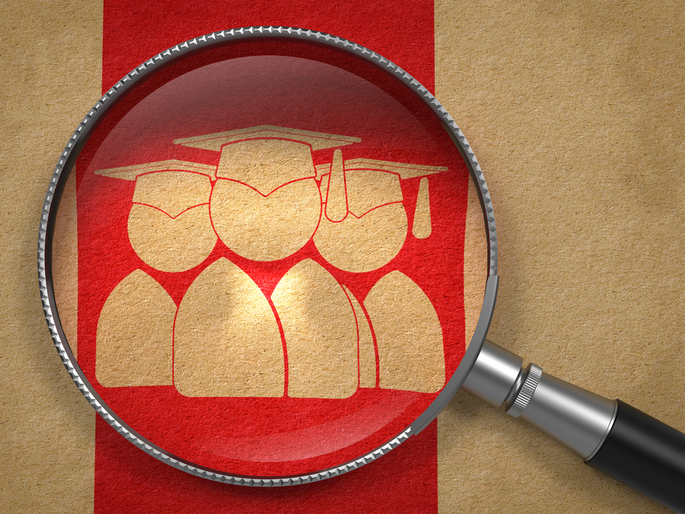 Magnifying Glass with Icon of Human Silhouettes in Grad Hat on Old Paper with Red Vertical Line Background. Education Concept.